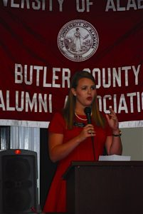 Lady in red dress standing behind podium with red Butler County Alumni Association banner in background.