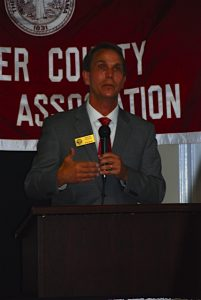 Man in Gray suit standing behind podium with red Butler County Alumni Association banner in background.