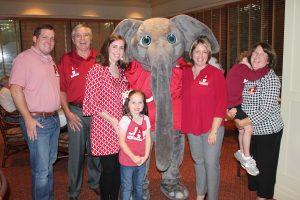 Group of people standing in room with Big Al Elephant in dim light room.