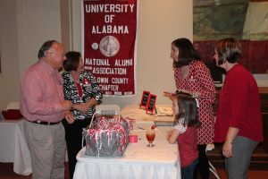 Group of people standing around table with red University of Alabama banner hanging on wall.
