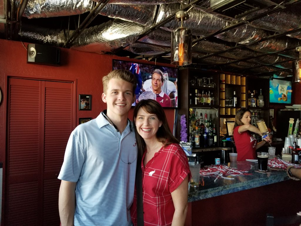 Man in blue shirt and women in red shirt standing in front of dark wall