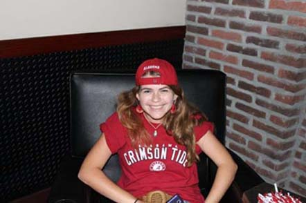 Girl sitting in brown chair with red shirt and cap on.
