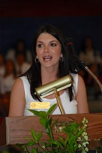 Lady standing behind podium in white top.
