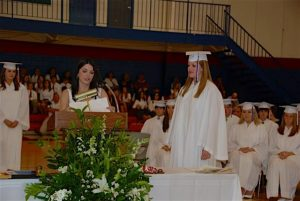Lady standing behind podium in white top and students in the background in white caps and gowns.