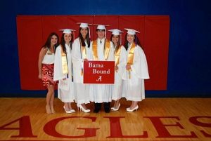 Group of students in white cap and gowns standing in front of red wall.