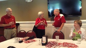 Two people with red shirts standing behind a table.