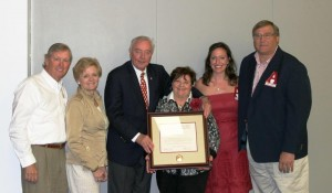 Group of people standing in room with white wall and lady in center holding plaque.