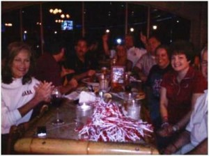 Group of people sitting at table in dim light room.