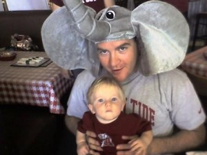 Man with Elephant Hat on holding a baby in crimson shirt.
