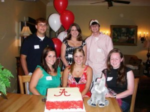 Group of people sitting at table with red and white cake.