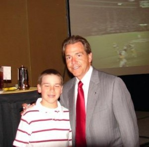 Coach Nick Saban standing with a student.