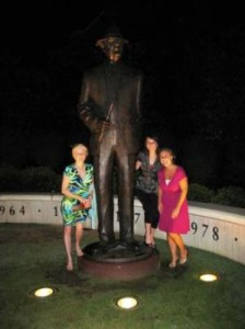 Group of people standing by statue at night.