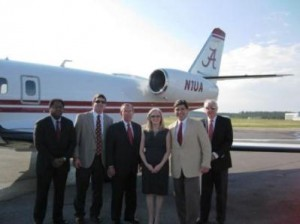 Group of people standing in front of airplane.