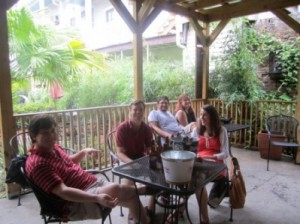 A group of people sitting at a patio table outside.