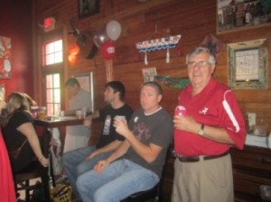 Two men sitting at at table and one man in red shirt standing.