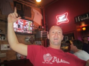 Man in a red shirt standing in a bar.