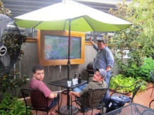 Two men sitting at a patio table with umbrella and one man standing by a TV Screen outdoors.