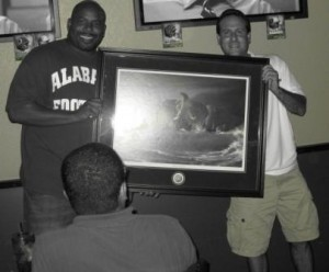Black and white photo of two men holding picture in frame.