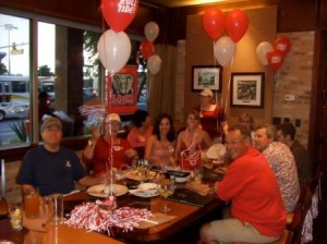 Group of people sitting at table with red and white balloons.