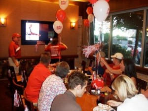 Group of people sitting in room with balloons on table. TV screen in background.