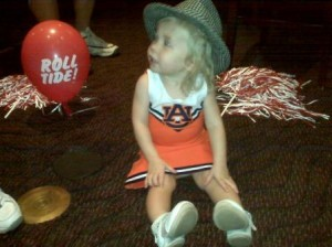 Little girl dressed in white and orange dress with houndstooth hat.