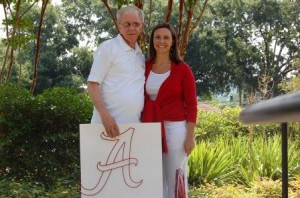 Man in white shirt and lady in red shirt standing outside holding a poster of an A.