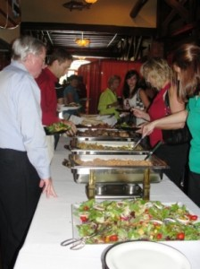 Group of people stanidng in a buffet line.