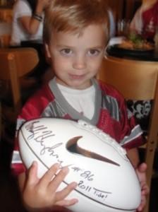 Little boy holding an autographed football.
