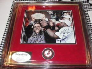 Framed picture with red mat of Coach Nick Saban and football team.