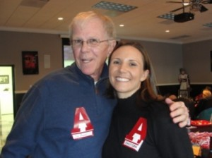 Man in Blue Jacket and Lady in Black Shirt standing in room with dim light.