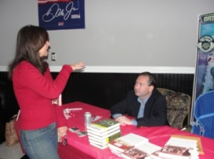 Women in red standing in front of table with red cloth. Man in Black jacket signing a book.