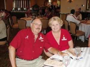 Man and lady in red shirts sitting at table in dim light room.