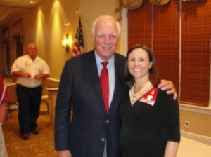 Man in black jacket and red tie standing by lady in black dress.