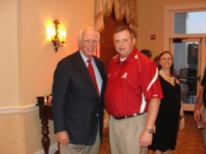 Man in black jacket and man in red shirt standing in room with dim light.