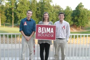 Group of people standing outside one in middle holding a red and white BAMA Bound sign.