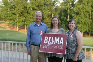 Three people standing outside and one holding a BAMA Bound sign.