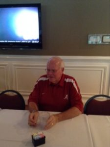 Man in red shirt sitting at a table with white wall in background.