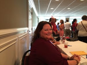 Lady in crimson top sitting at a table.