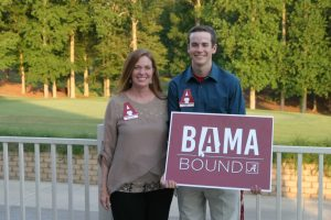 Two people standing outside holding a red and white BAMA Bound sign.