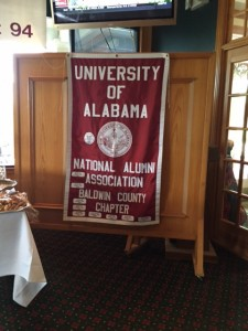 Red and white Univeristy of Alabama banner on brown wall.