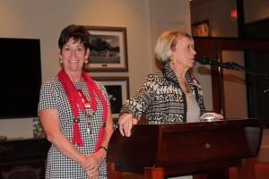 Two ladies standing behind podium in dim light room.