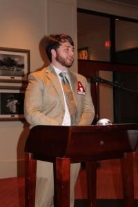 Man in beige suite standing behind podium in dim light room.