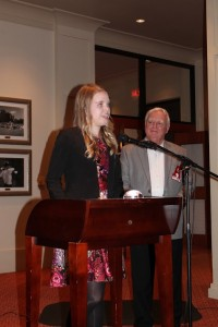 Lady in dark jacket standing at podium with man in gray jacket in dim light room.