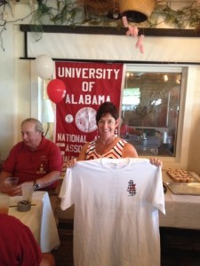 Man in red shirt and lady holding white t-shirt in room with red/white University Banner in background.