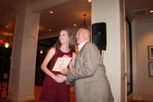Dean Chuck Karr presenting a certificate to student in crimson dress in front of white/brown wall.