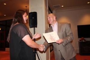 Dean Chuck Karr presenting a certificate to student in dark top.