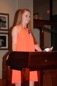 Student in orange dress standing behind podium.