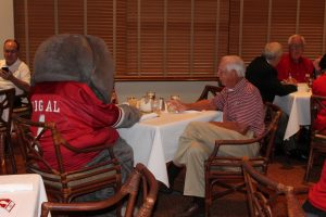 Big Al and man sitting at table in room with brown shades.
