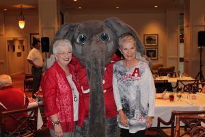 Two ladies standing with Big Al Elephant in room with dim light.