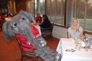 Big Al Elephant sitting at table with lady in front of window with shades.